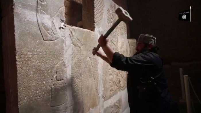 """April 11, 2015: In this image made from video posted on a militant social media account affiliated with the Islamic State group purports to show a militant taking a sledgehammer to an Assyrian relief at the site of the ancient Assyrian city of Nimrud, which dates back to the 13th century B.C., near the militant-held city of Mosul, Iraq. The destruction at Nimrud, follows other attacks on antiquity carried out by the group now holding a third of Iraq and neighboring Syria in its self-declared caliphate. The attacks have horrified archaeologists and U.N. Secretary-General Ban Ki-moon, who last month called the destruction at Nimrud """"a war crime."""" (Militant video via AP)"""